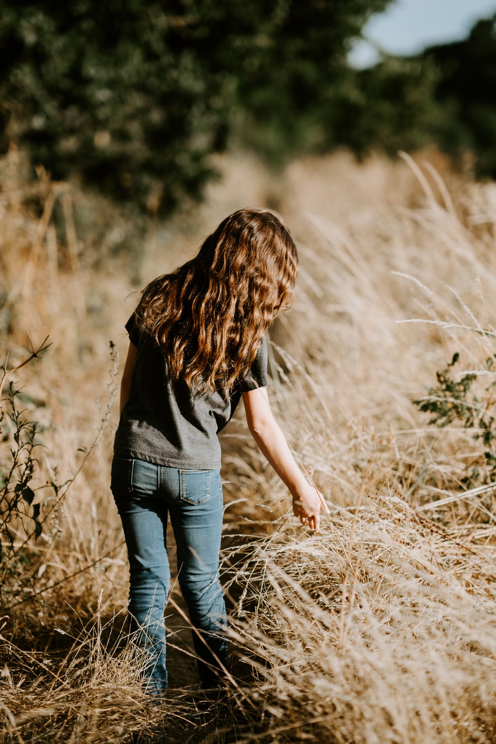woman standing in middle of grass field