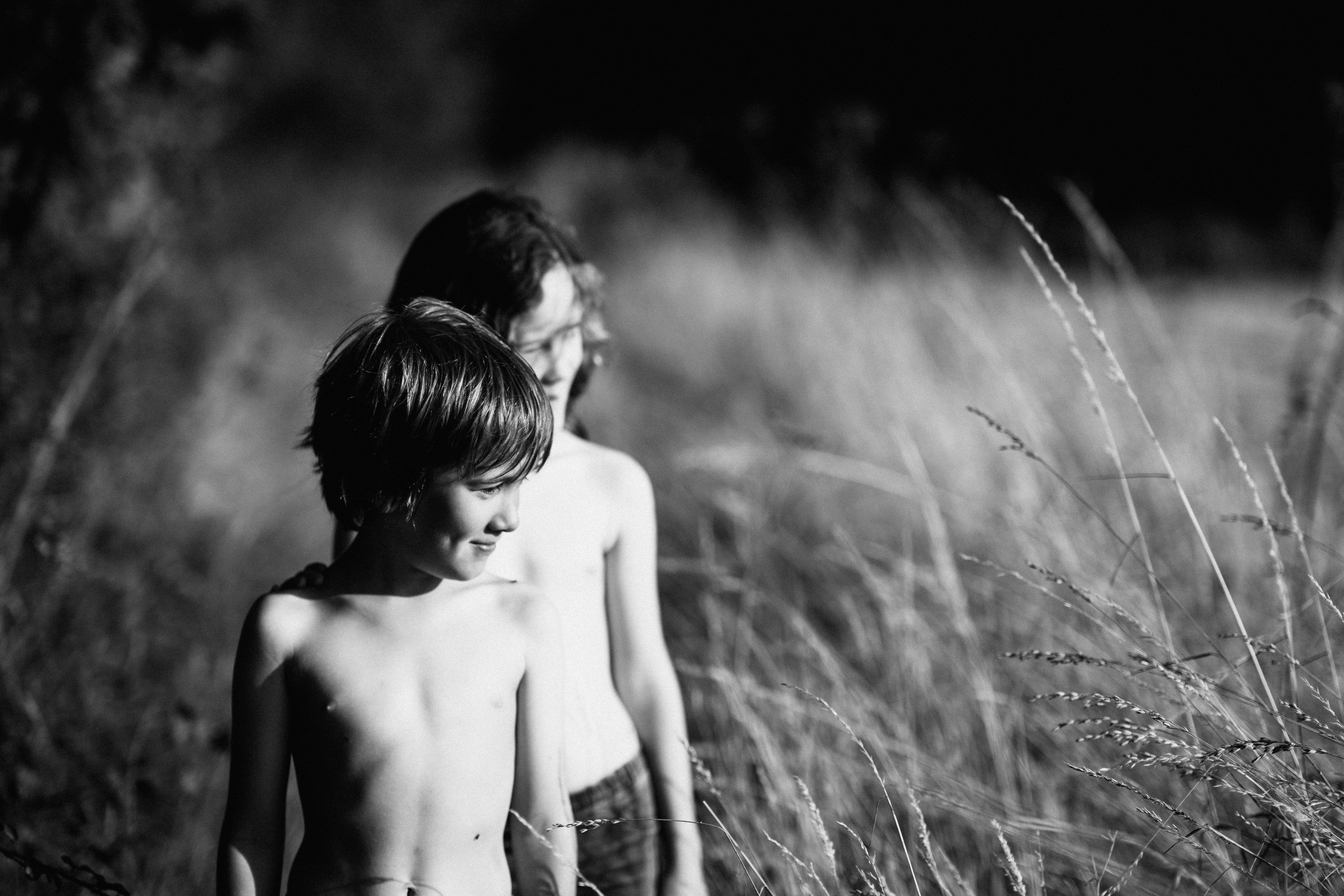 two topless toddlers standing on open field