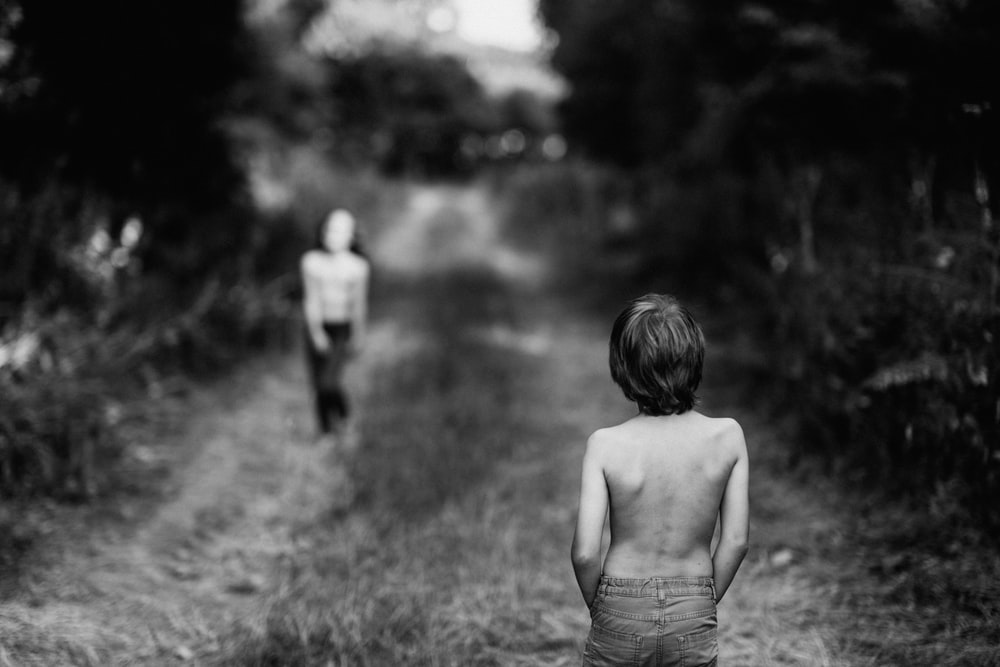 grayscale photography of topless boy on pathway facing girl