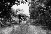 grayscale photo of boy and girl walking on path