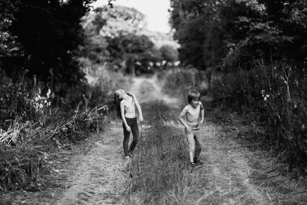 boy and girl on footpath between grass grayscale photography