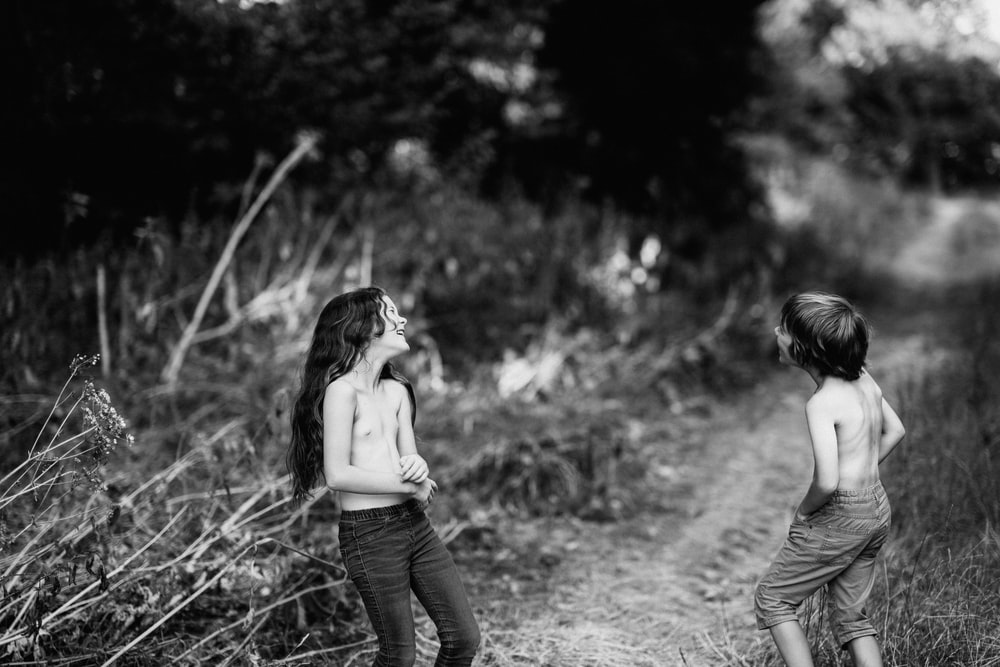 grayscale photography of girl and boy beside bush