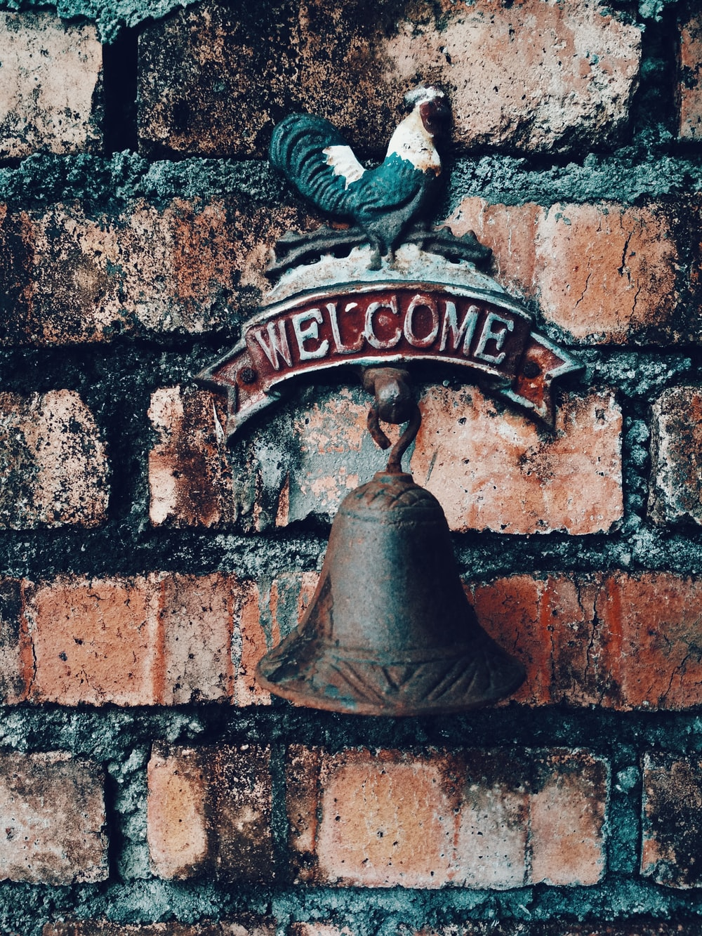 brown metal welcome bell on brown brick wall