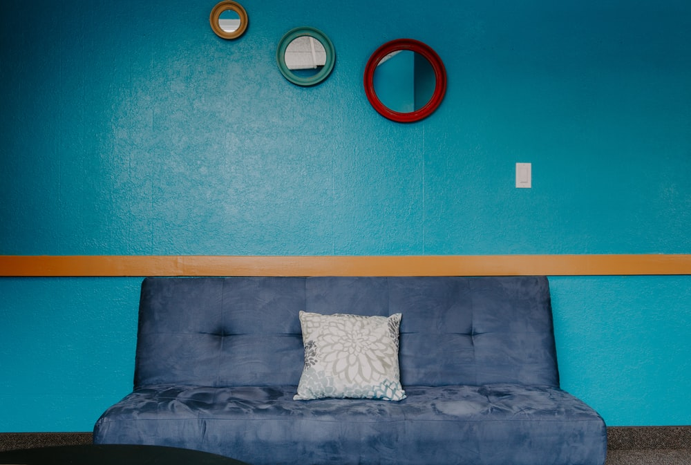 blue 3-seat sofa with throw pillow