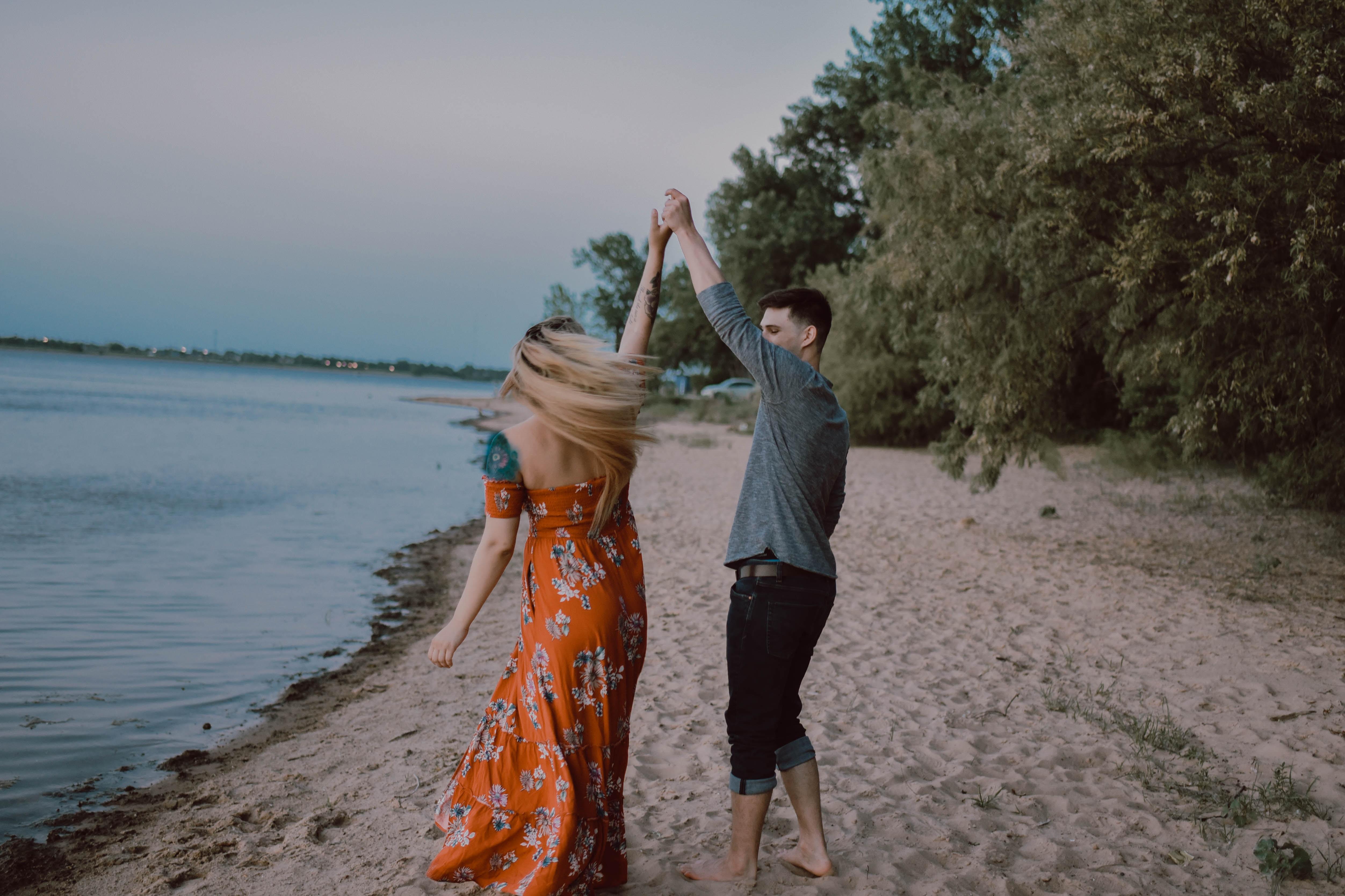 man and woman holding hands near seashore at daytime