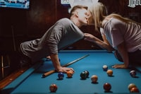 man and woman kissing on pool table