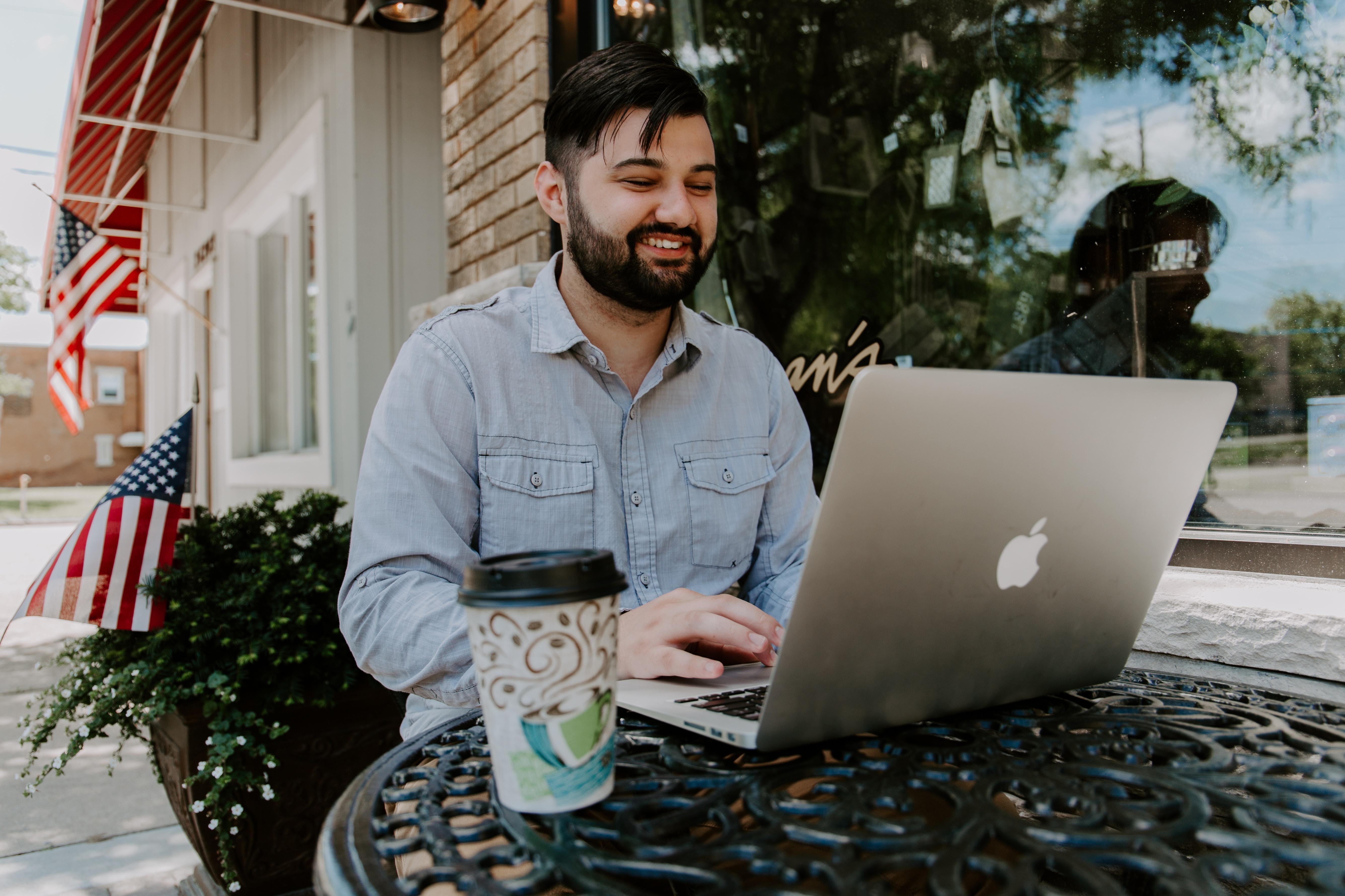 man in gray denim dress shirt smiling while using MacBook Pro