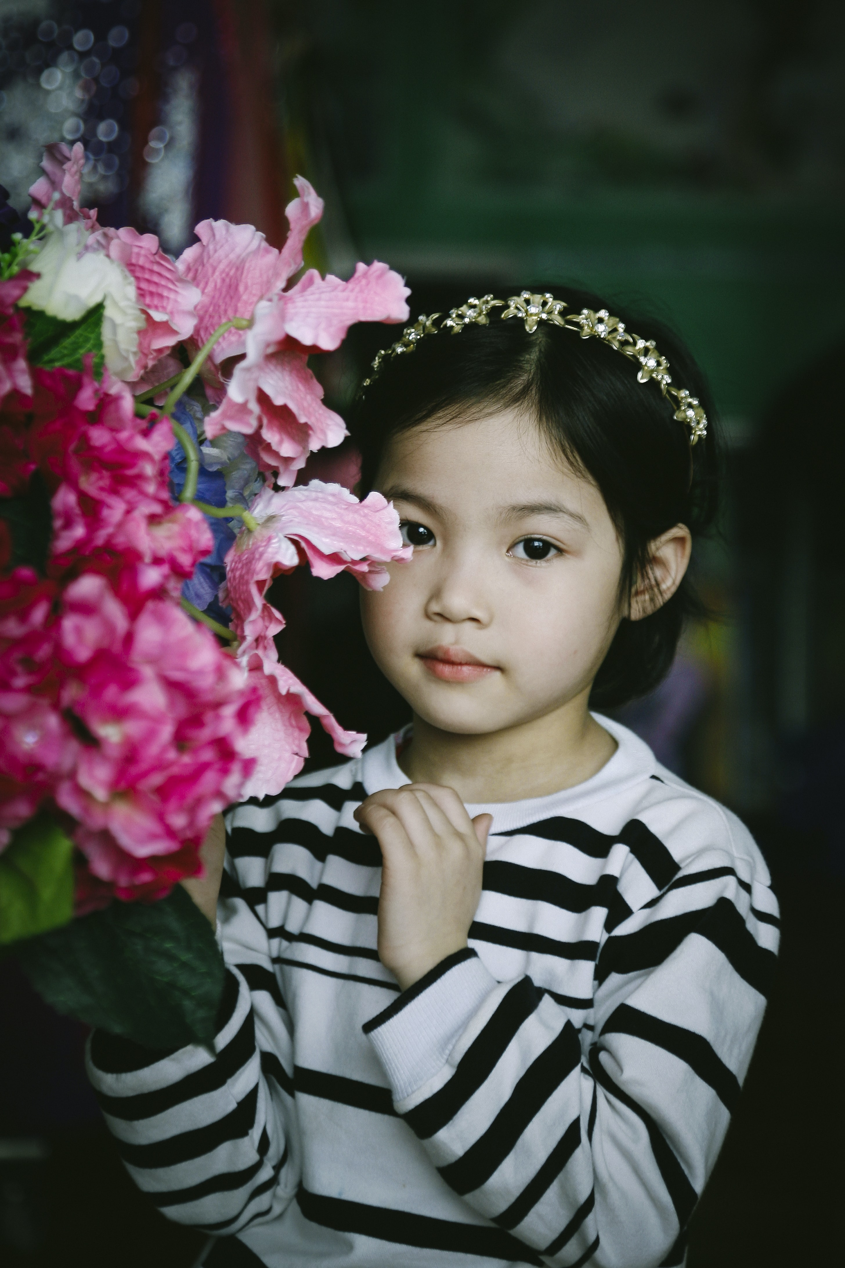 selective focus photography of girl beside pink petaled flowers