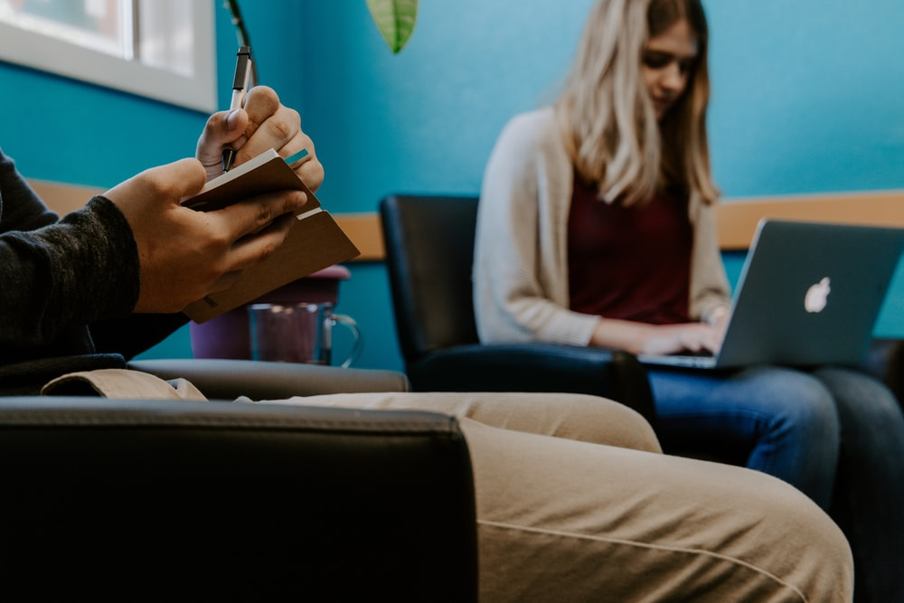 woman using MacBook Air beside man writing on book