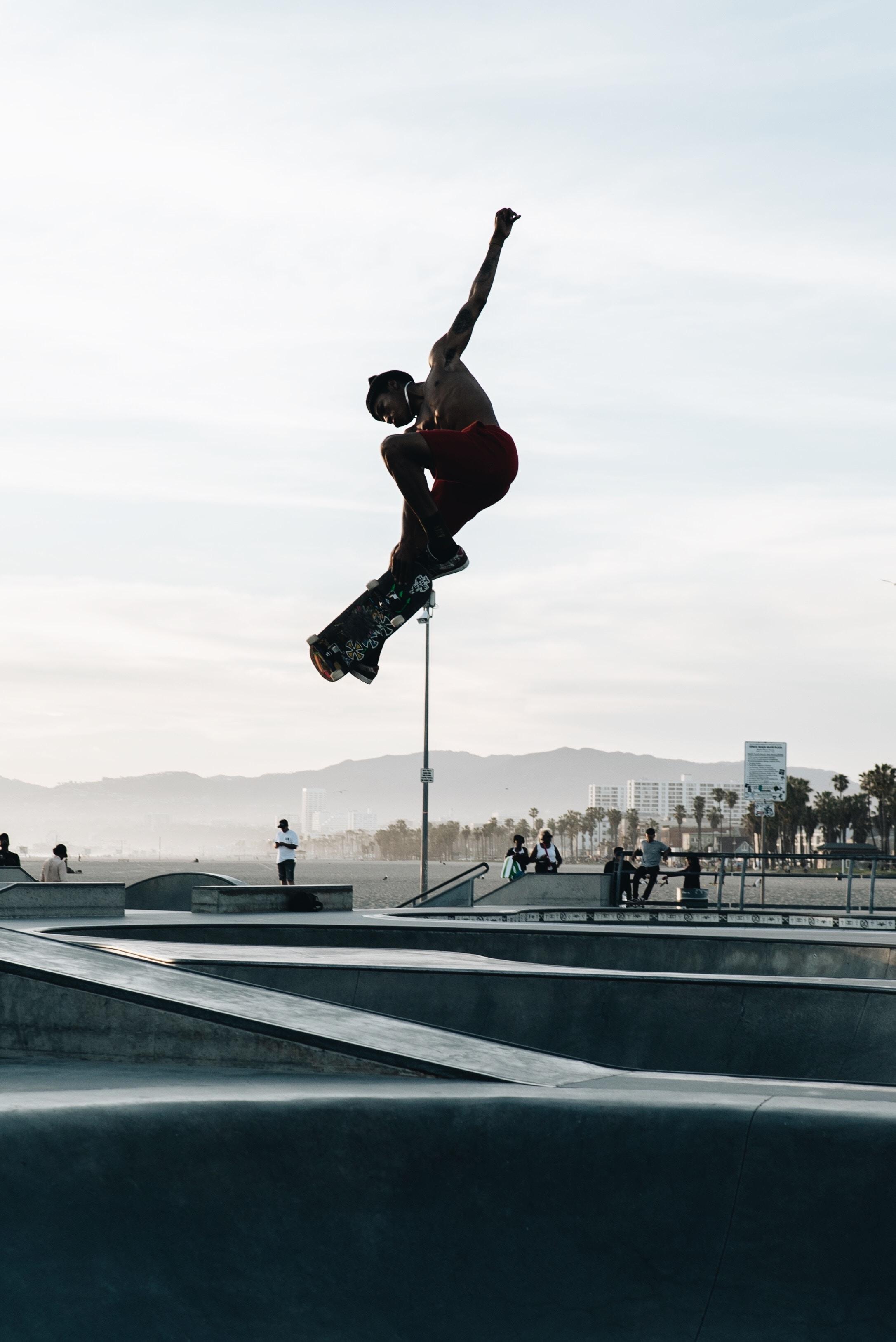 man wearing red shorts doing tricks on skateboard in skate park during daytime
