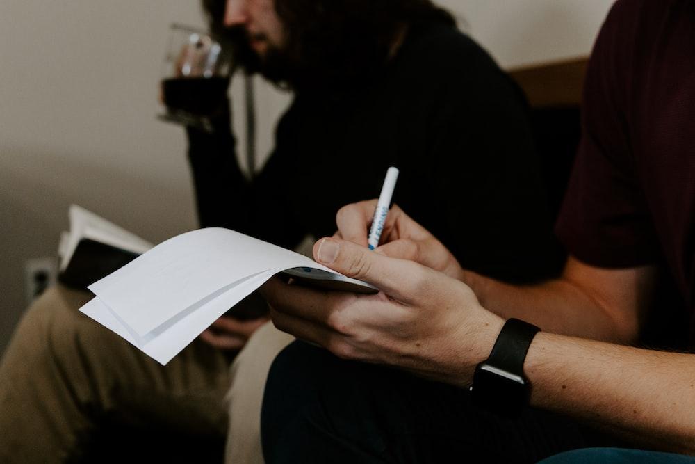 man writing beside man