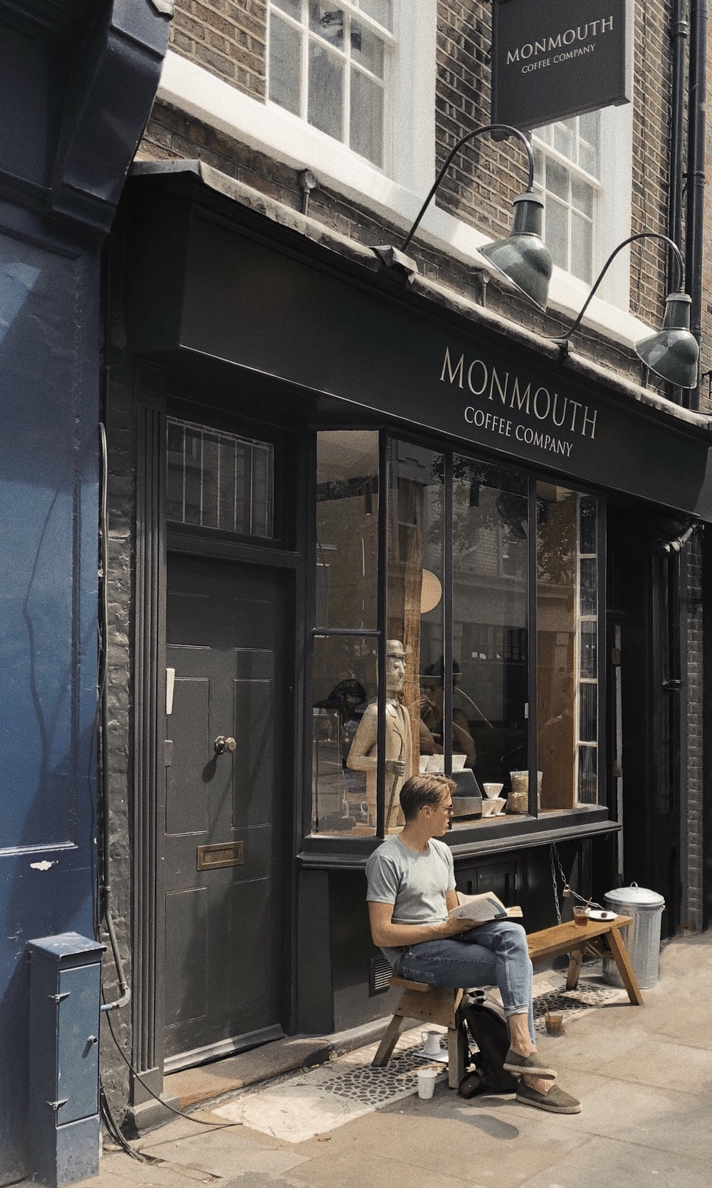 man sitting on bench in front of Monmouth store during daytime