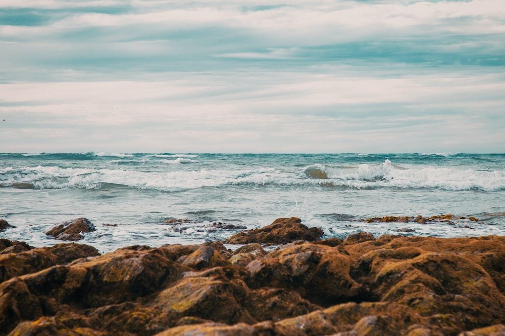 rocky coastline facing rippling body of water