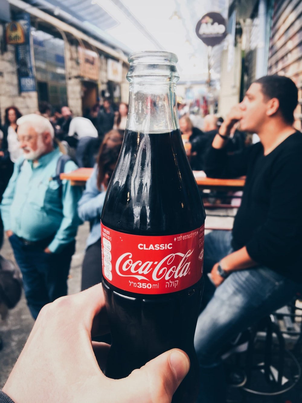 person holding 350 ml clear glass Coca-Cola soda bottle
