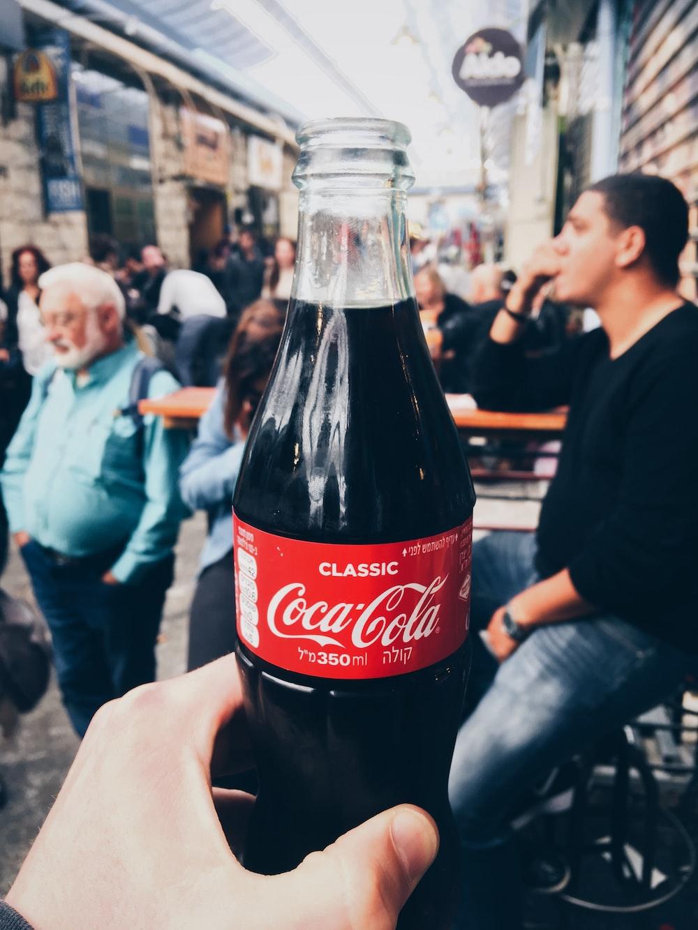 person holding 350 ml clear glass Coca-Cola soda bottle