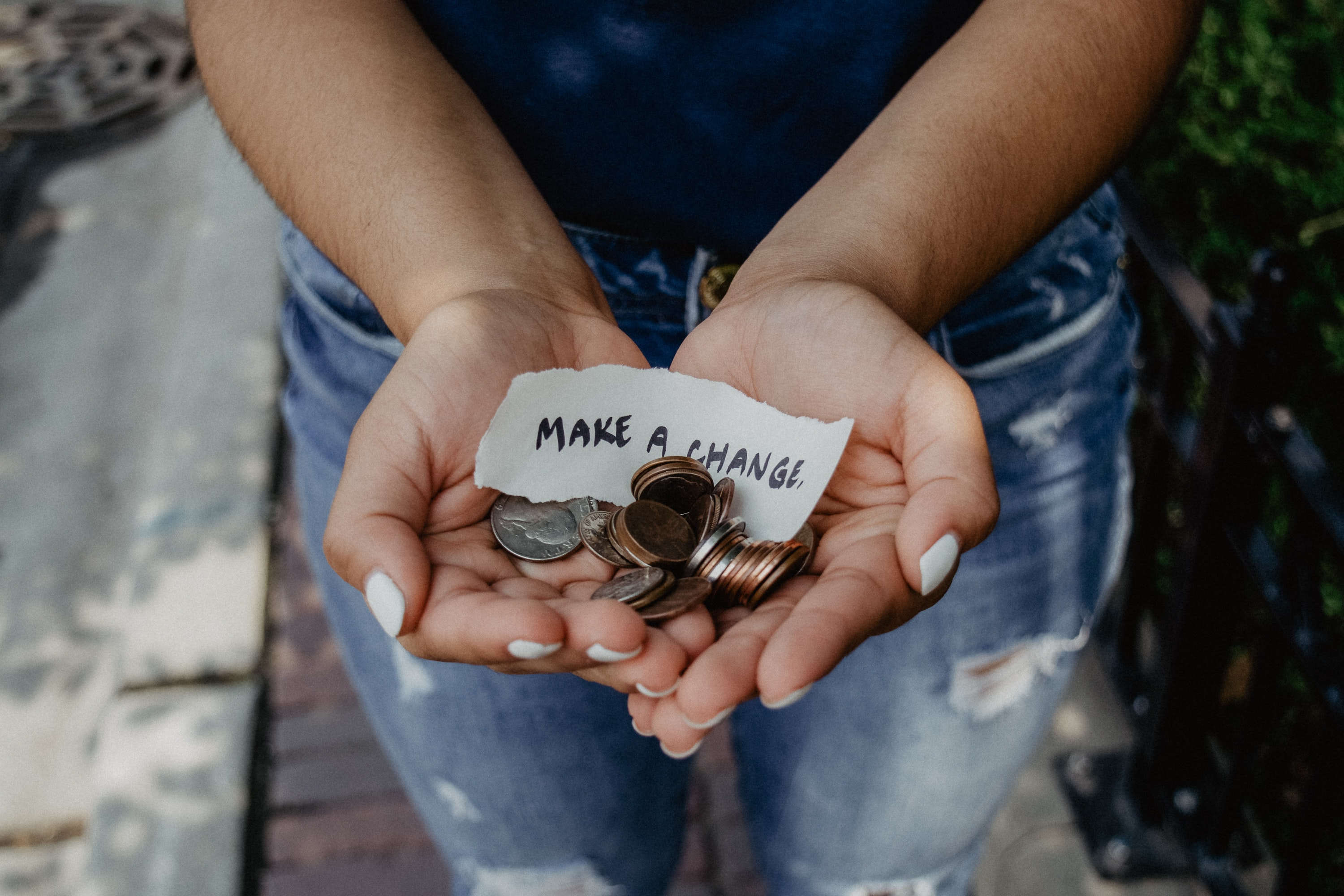 person showing both hands with make a change note and coins