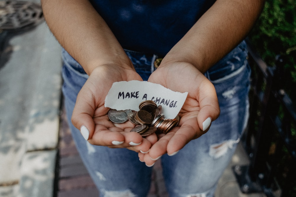 person showing both hands with make a change note and coins. Corporate Social Responsibility.