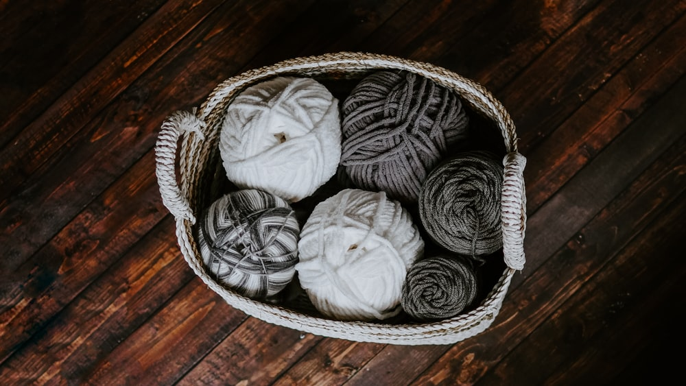 white and brown yarn in basket e