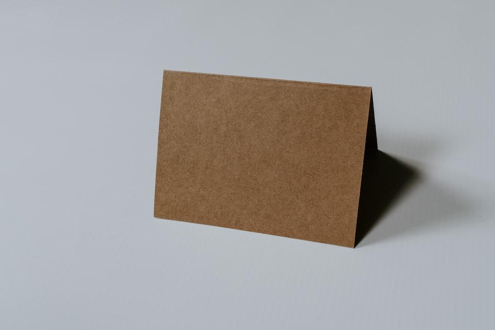 brown hardbound book on white surface