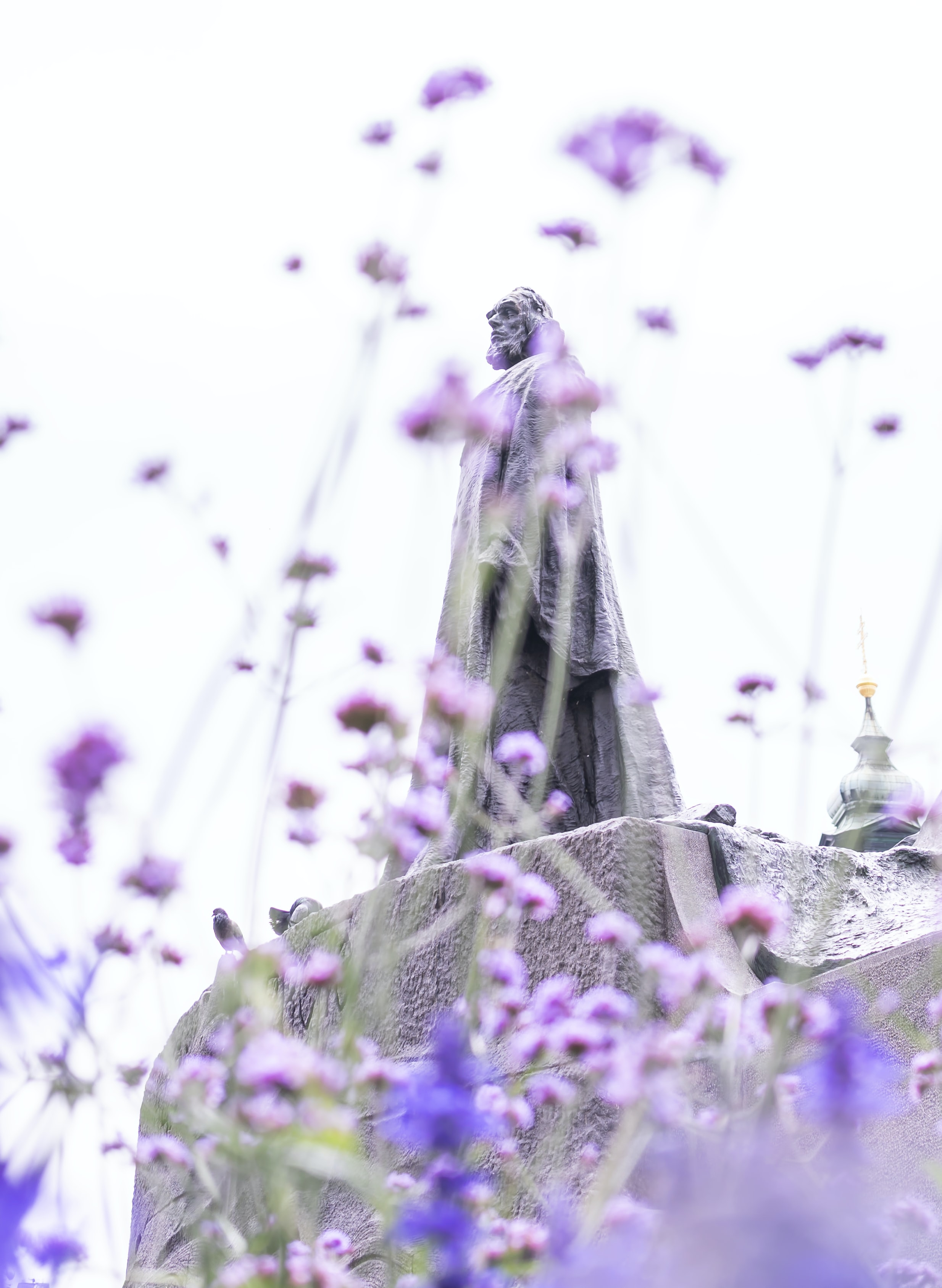 low angle photo of man wearing cloak statue under clear sky