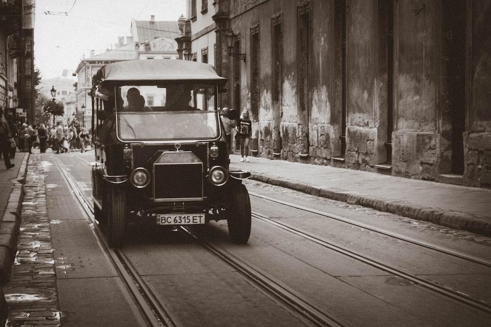 vintage black vehicle on road near building at daytime
