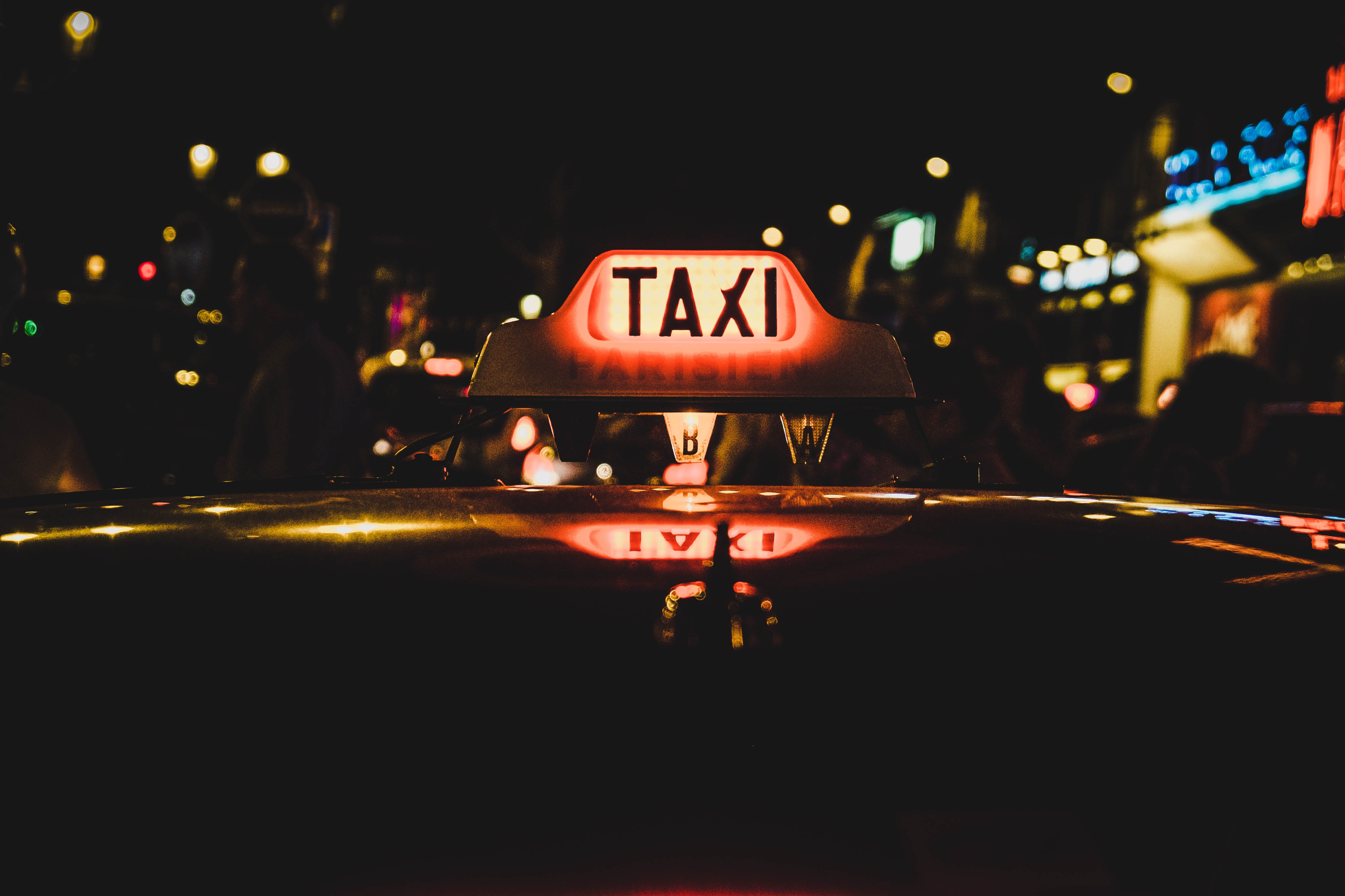 white and red Taxi beaconfield at nighttime