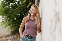 woman wearing pink sleeveless top leaning on wall