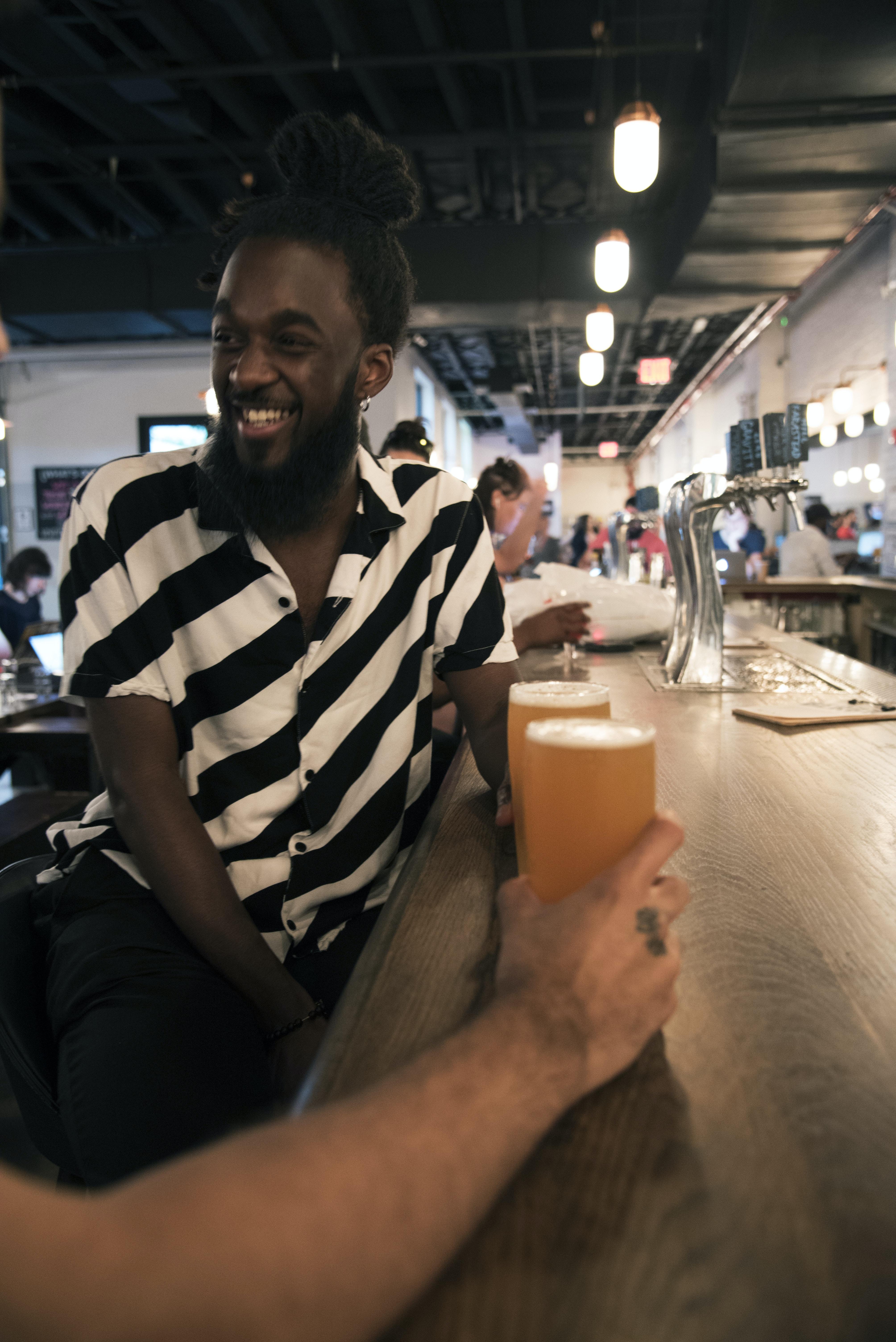 man sitting on stool in bar