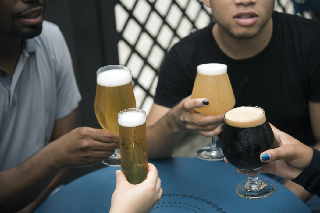 four people drinking beers