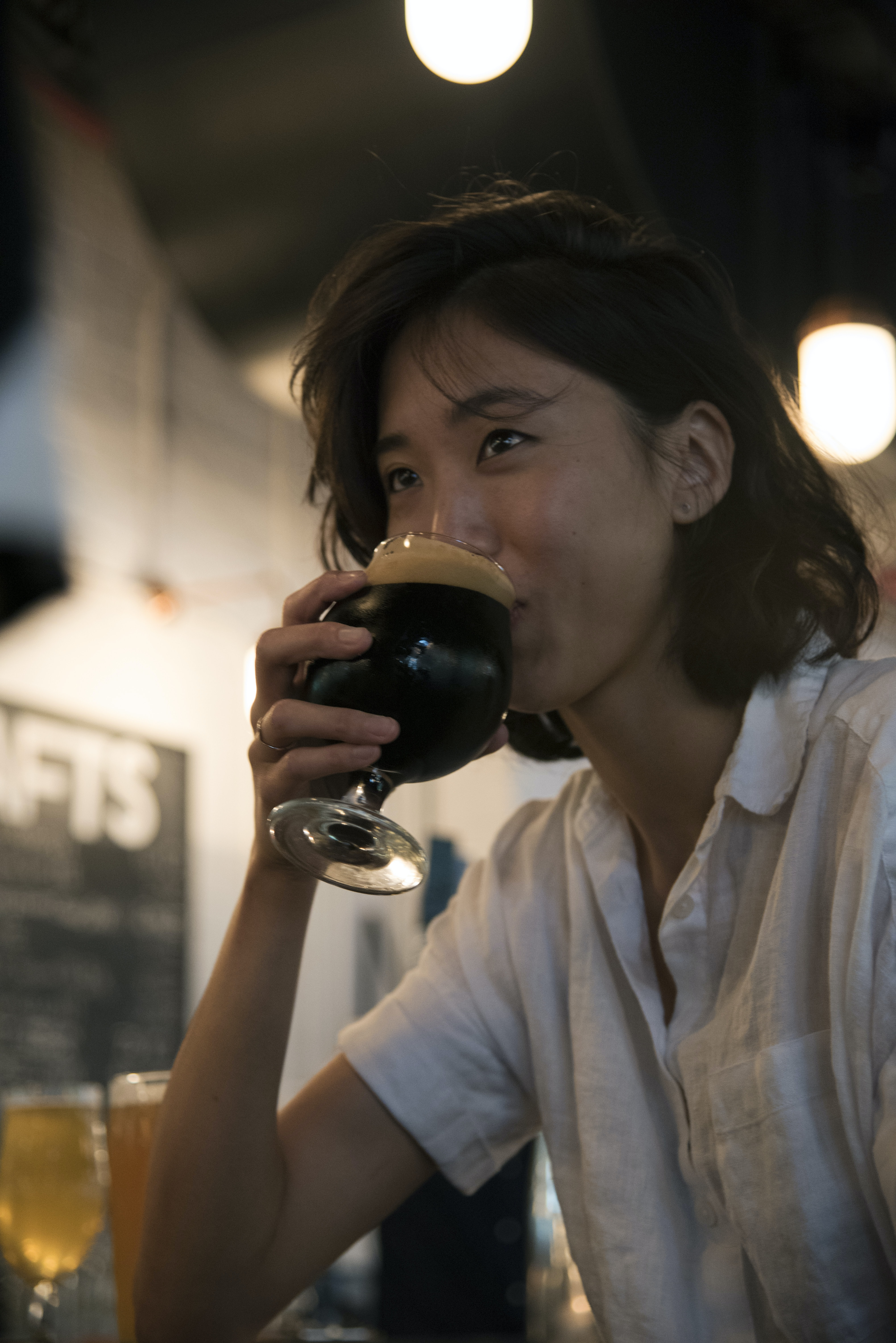 selective focus photography of woman drinking from short-stemmed glass