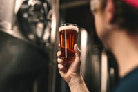 selective focus photography of person holding clear drinking glass