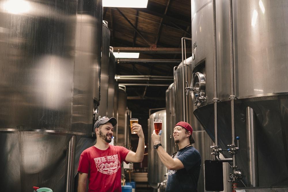 two men tasting beer near cylindrical tanks