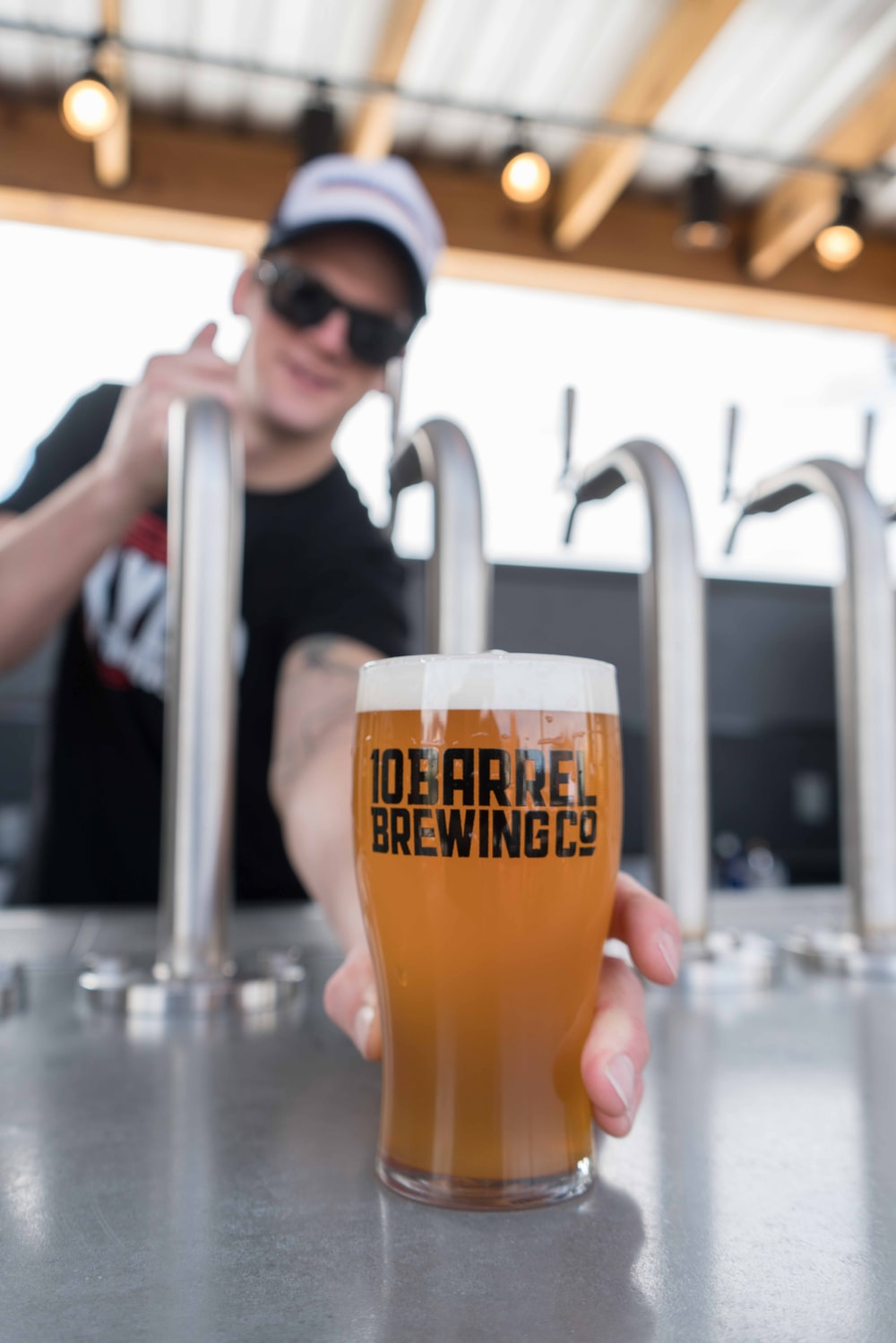 person holding 10 Barrel Brewing Co.-printed pilsner glass