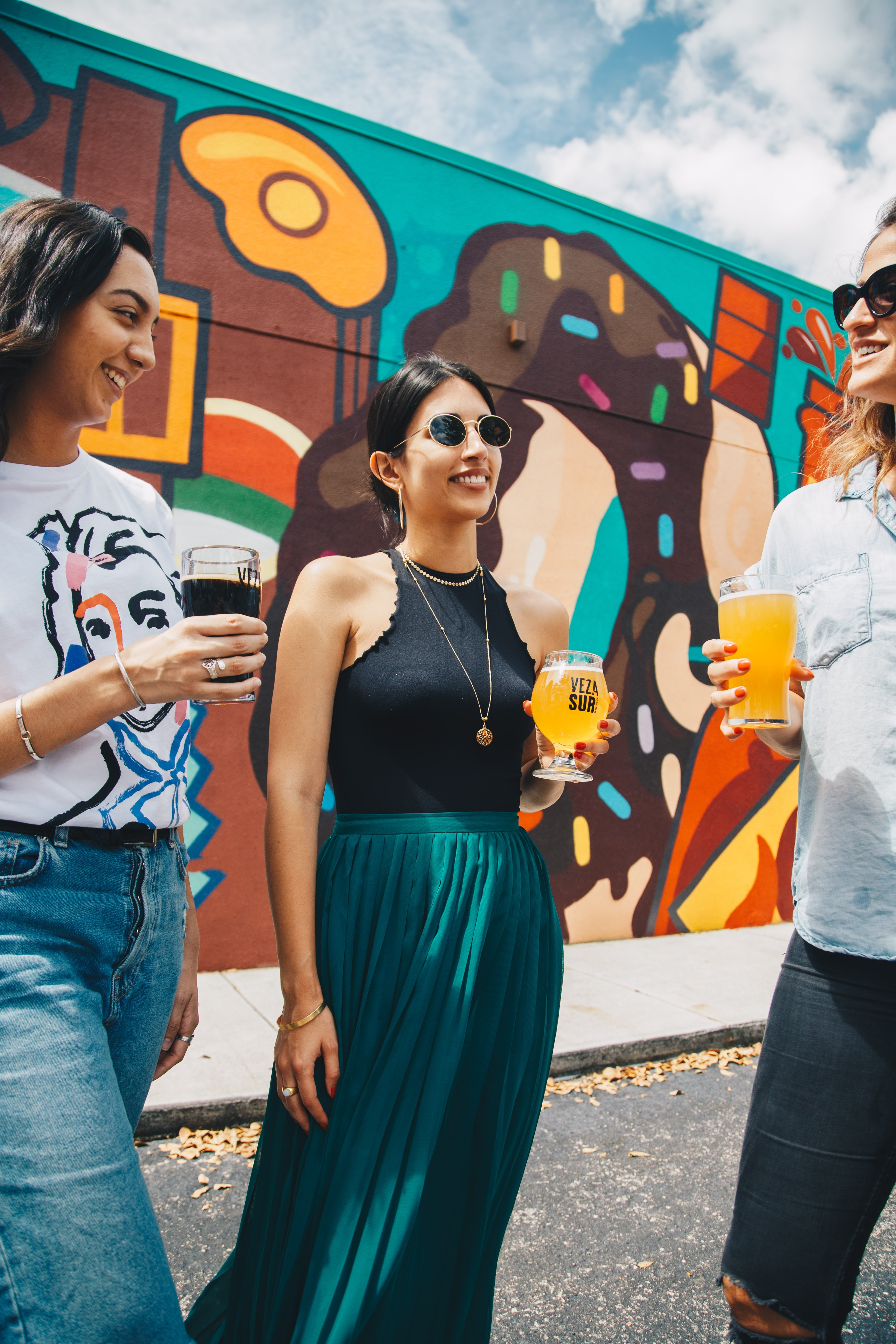 three women having a drink standing in front of wall graffiti