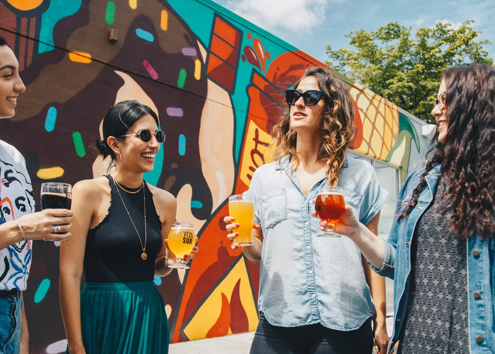 four women talking to each other holding clear drinking glasses while standing near wall with graffiti during daytime