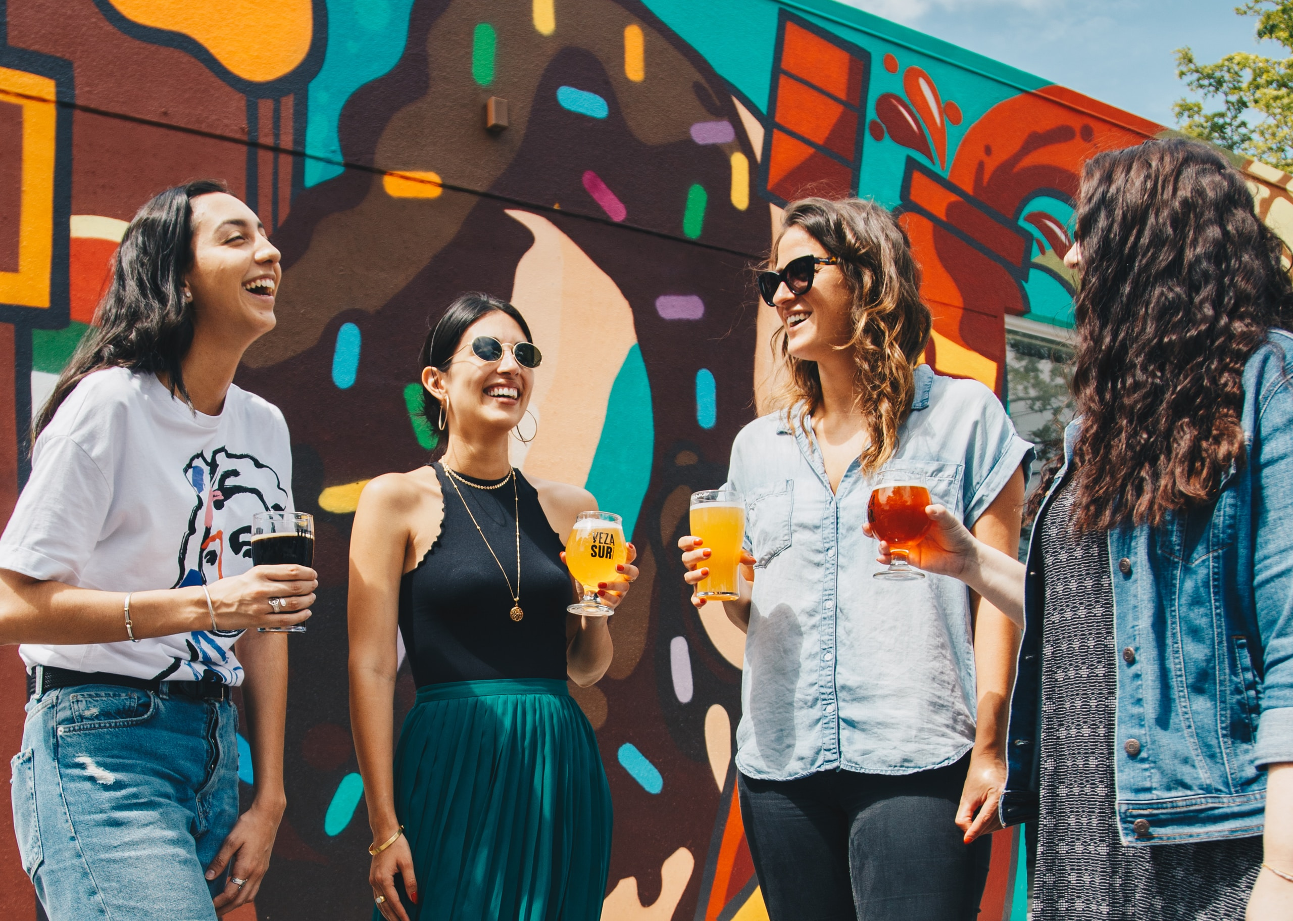 four women holding drinks while laughing together during daytime