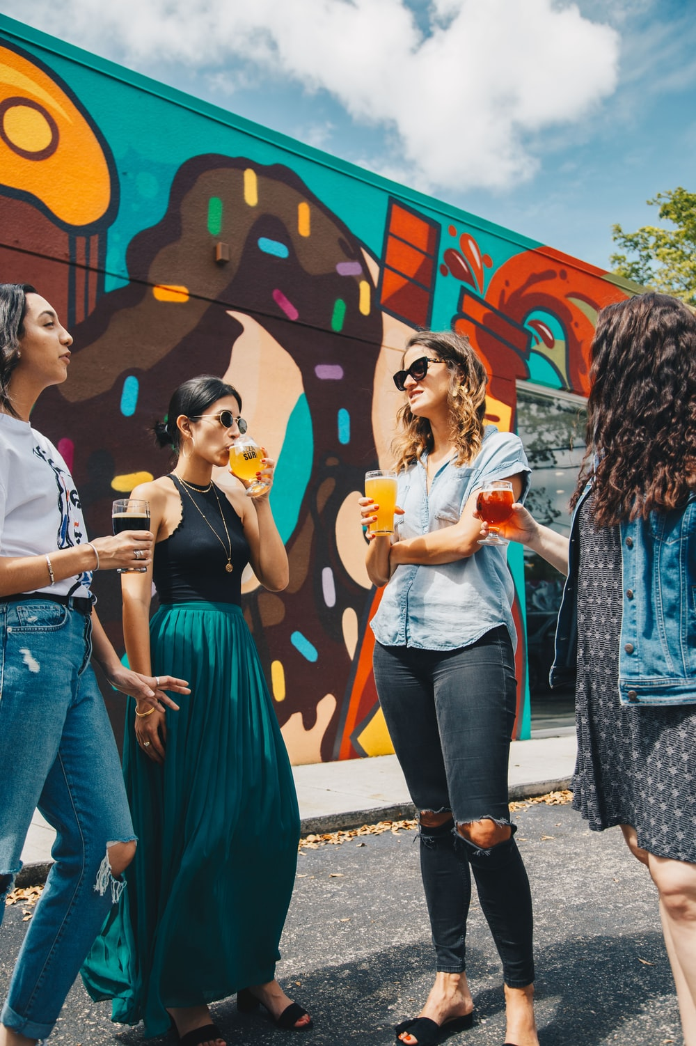four women holding fruit drinks standing near multicolored wall