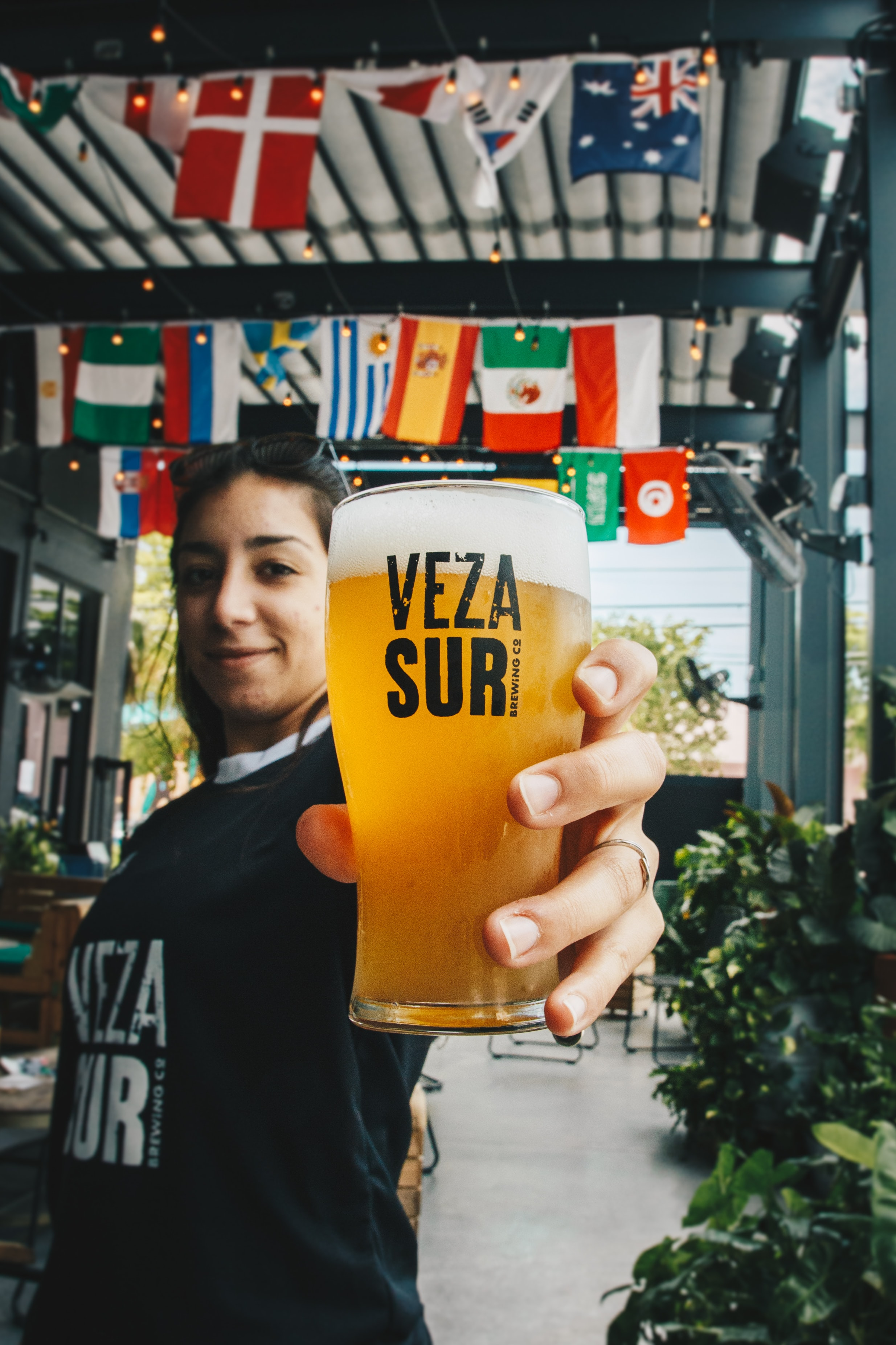 filtered photography of woman holding beer-filled Veza Suri pilsener glass
