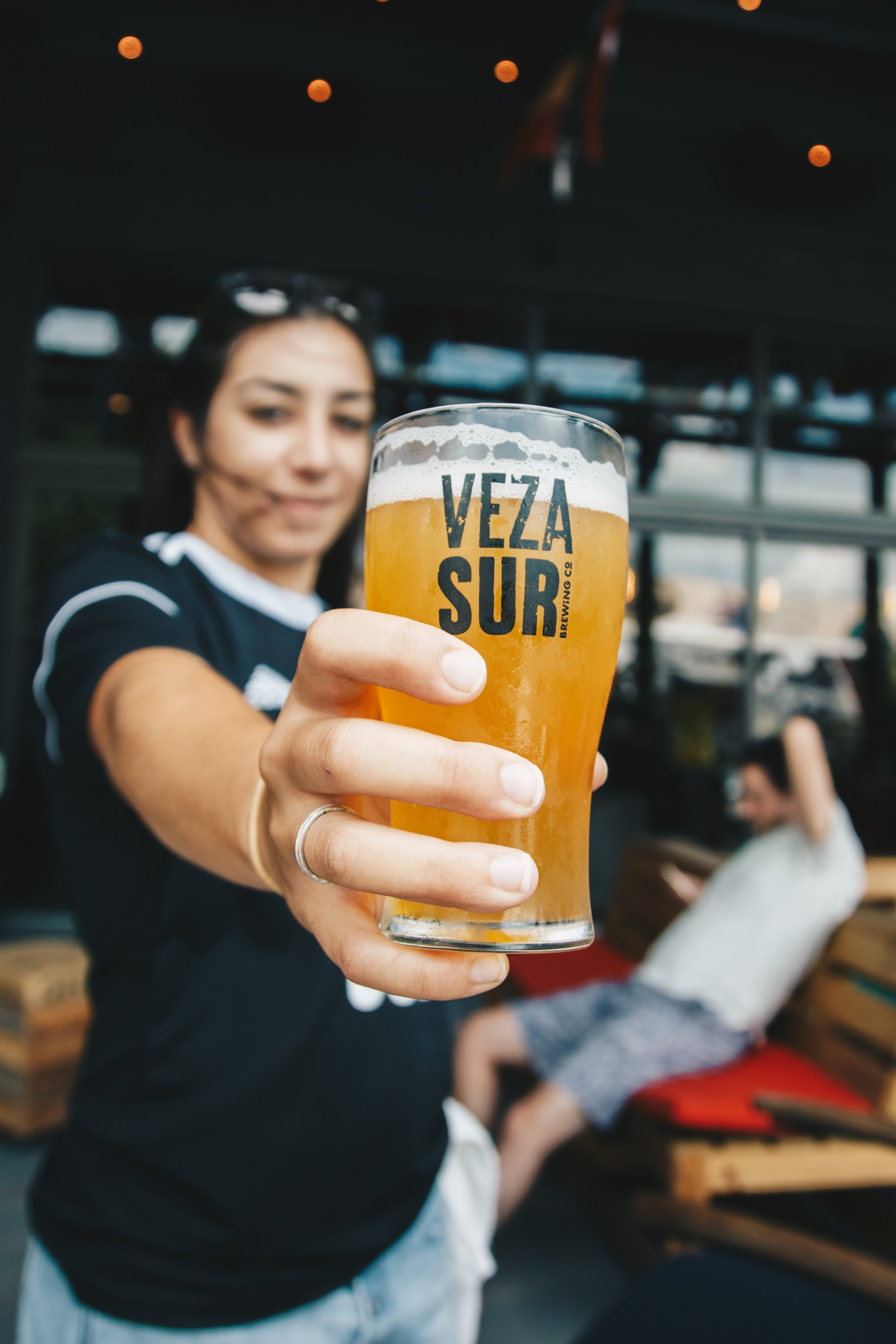 woman holding Veza Sur drinking glass cup filled with beer