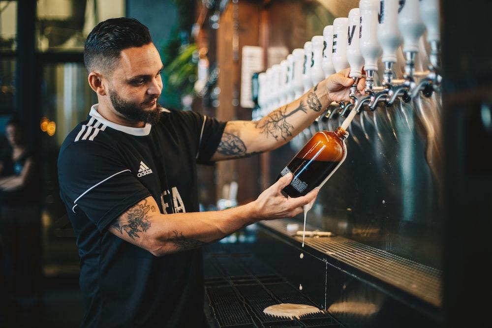 man holding brown glass bottle