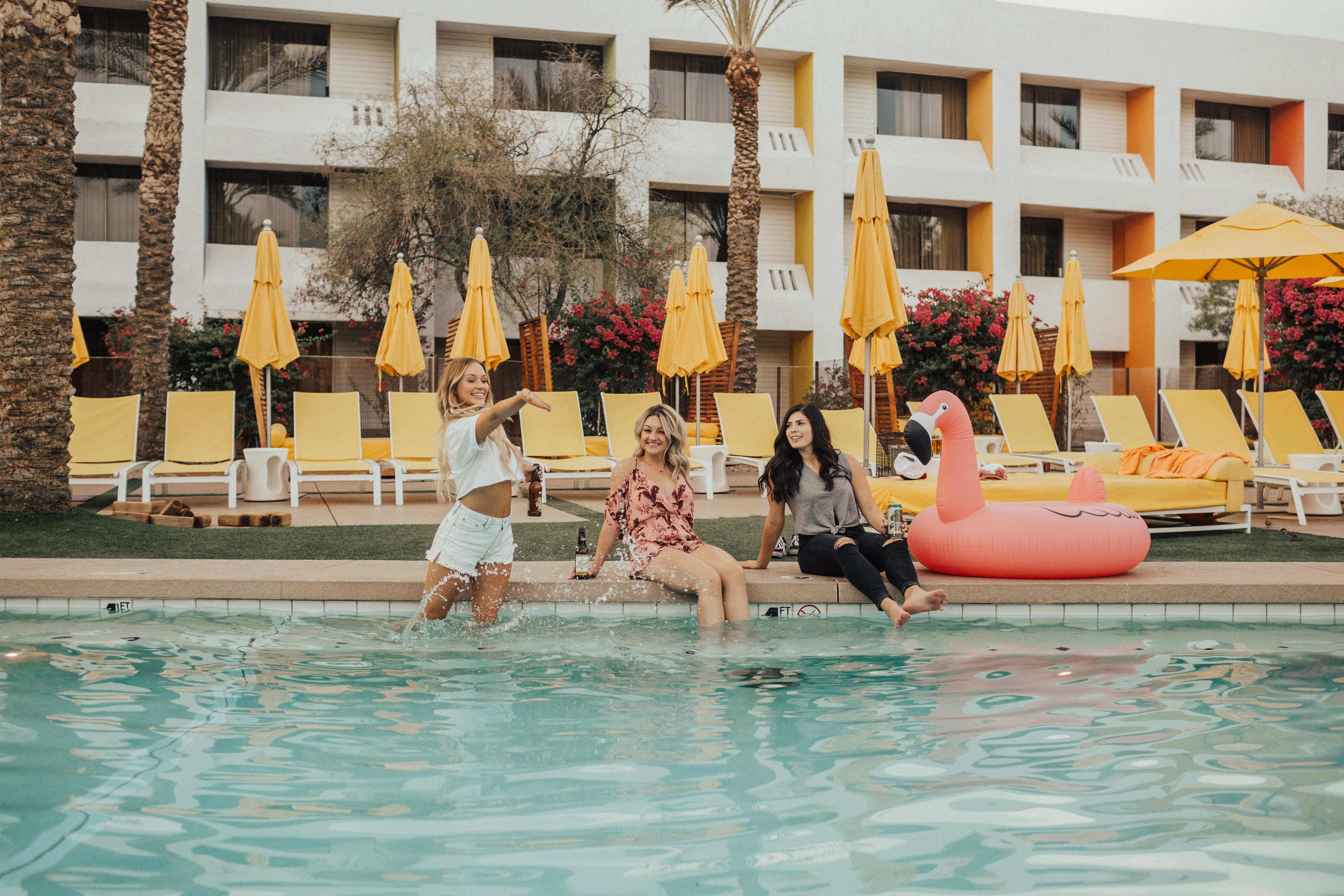 three women sitting beside flamingo floater near swimming pool during daytime