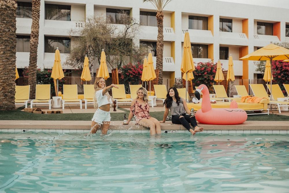 three women sitting beside flamingo floater near swimming pool during daytime