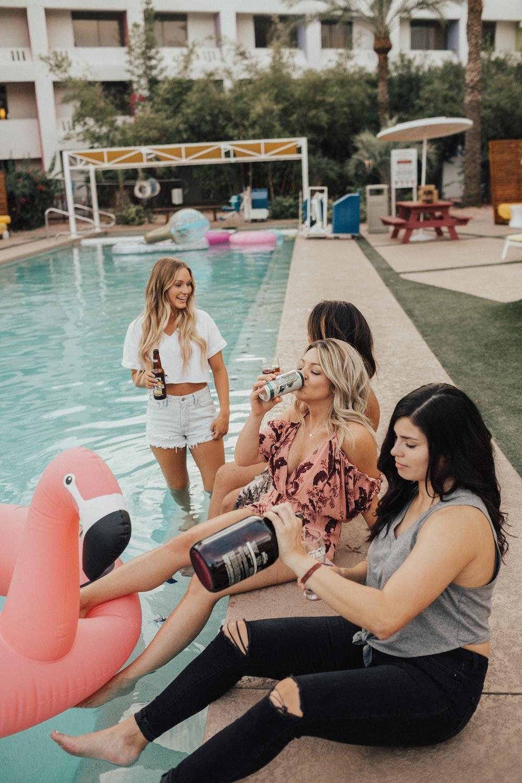group of women sitting near swimming pool