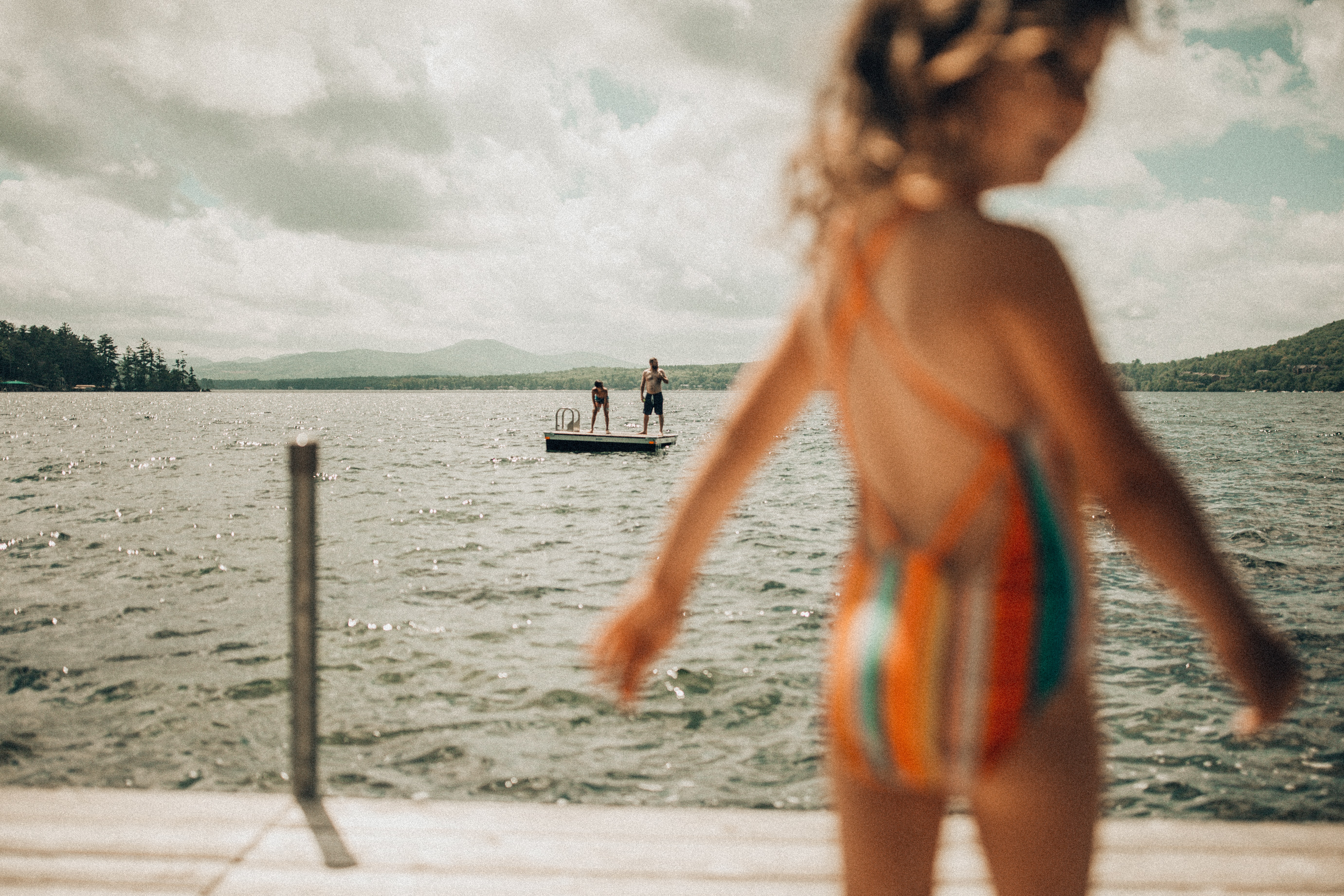 selective focus photography of two person standing on platform on body of water