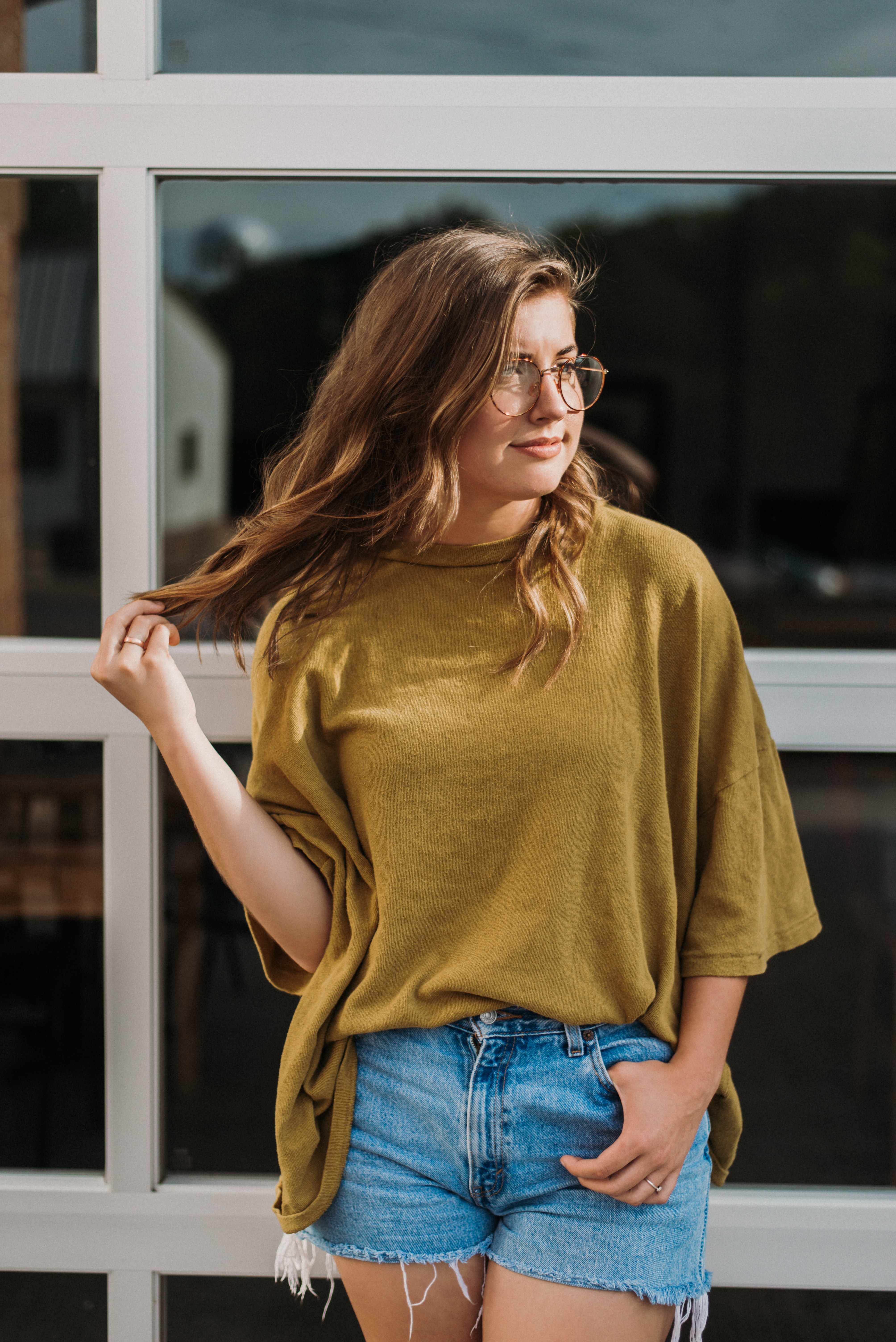 woman wearing brown crew-neck blouse standing near the glass building