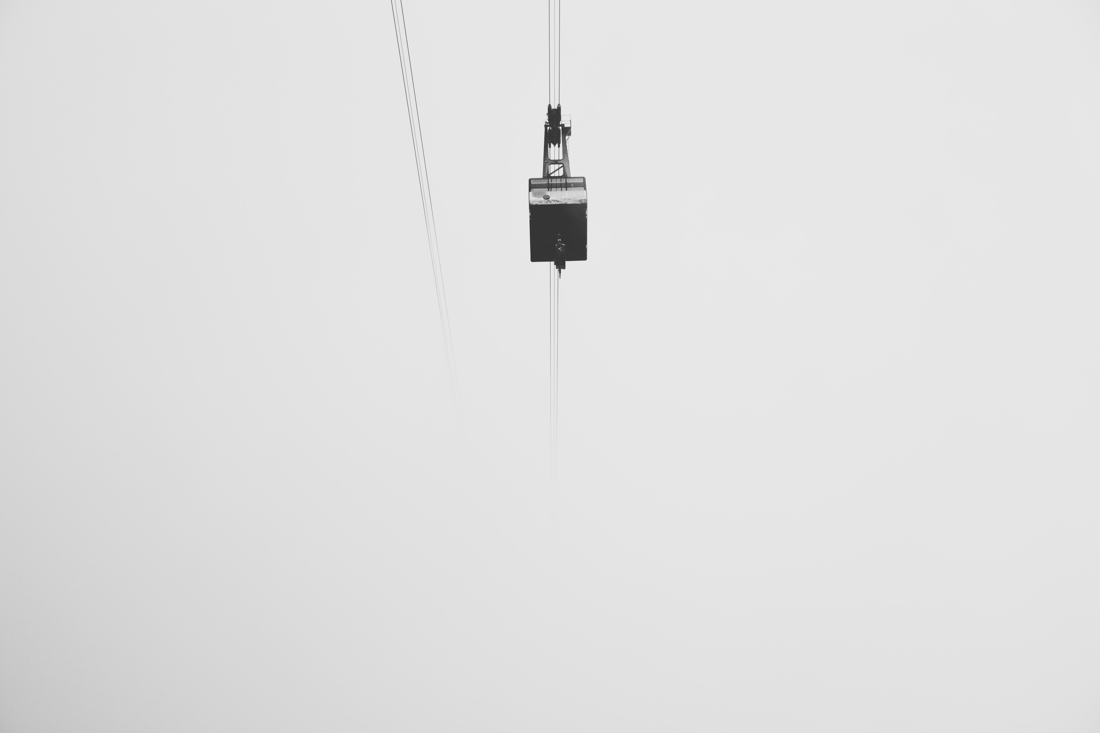 low-angle photography of cable car under gray skies