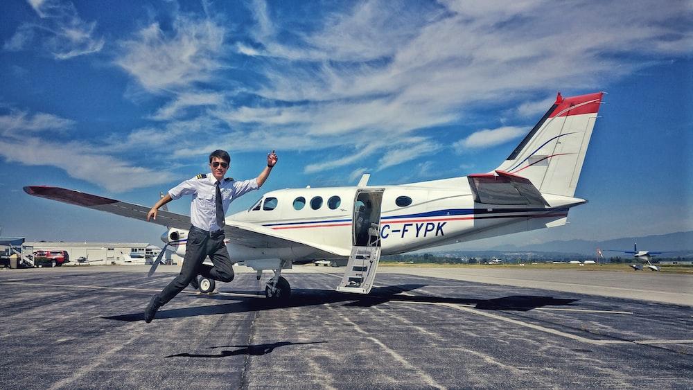 pilot jumping near aircraft