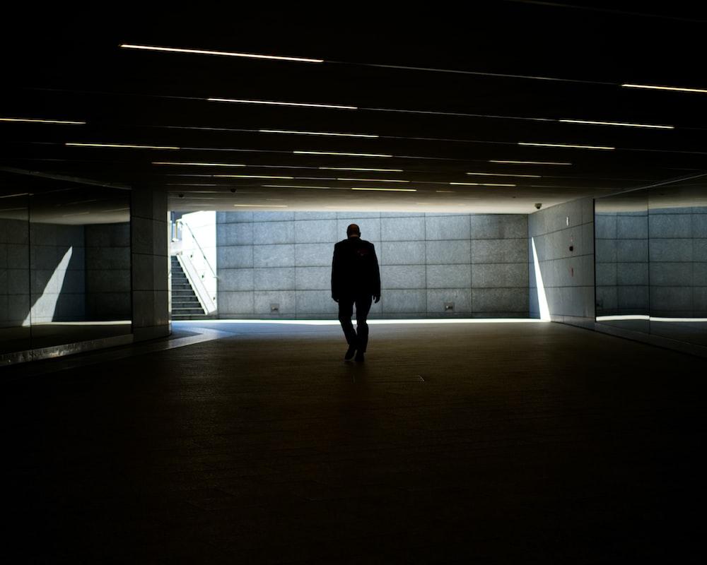 silhouette photo of person walking inside dark room
