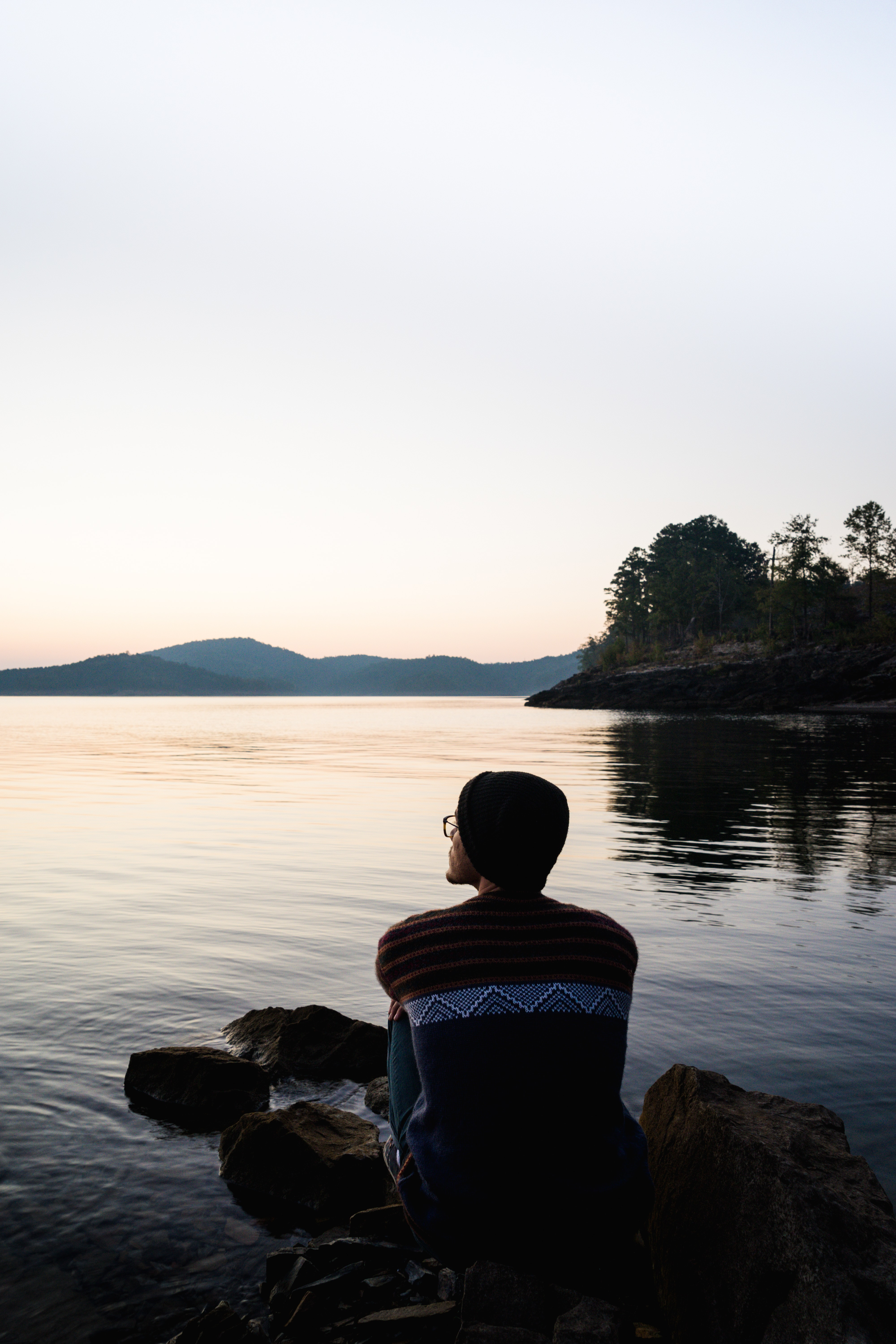 person sitting on rock near body of water