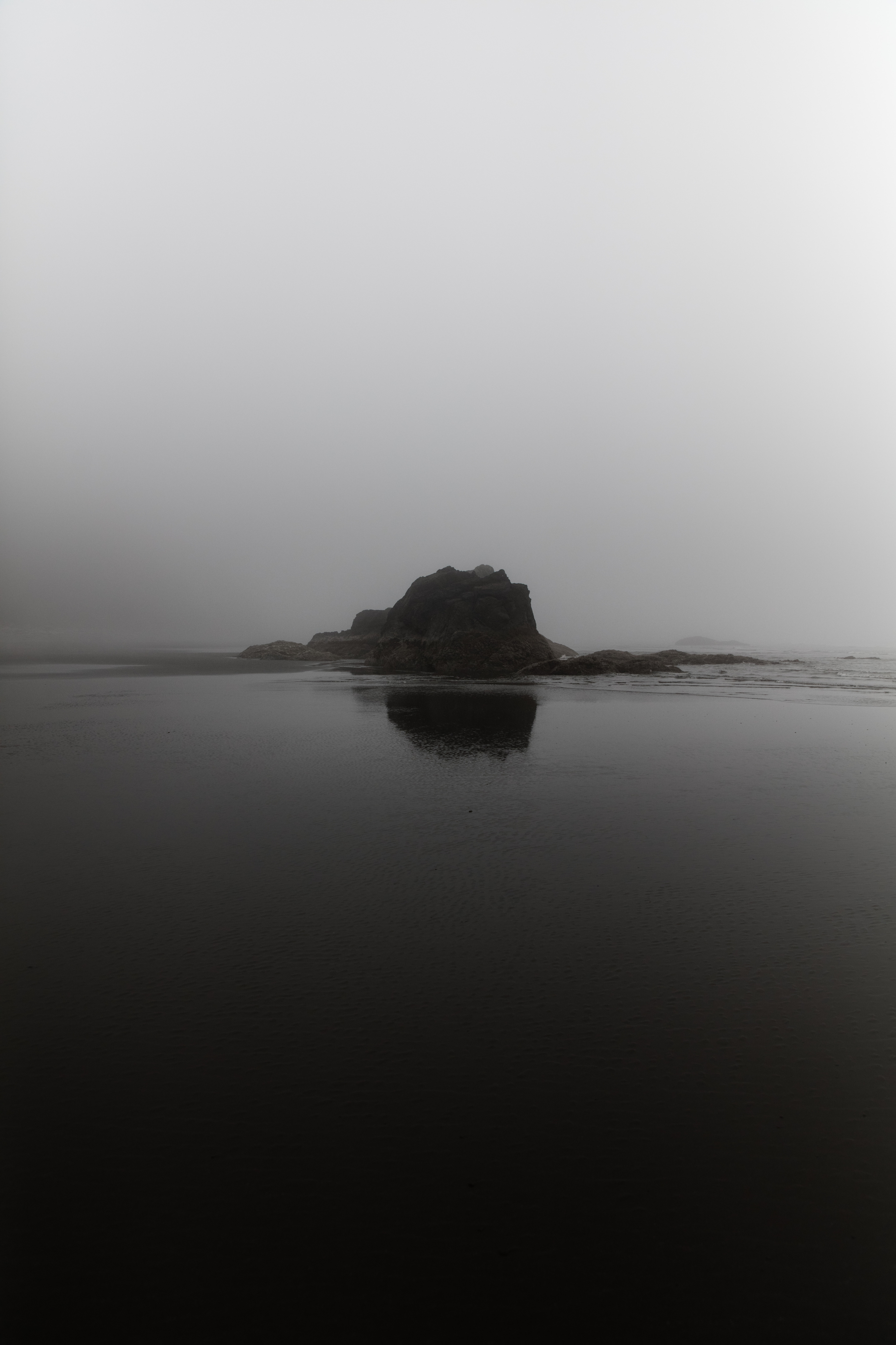 silhouette of rock formation in front of body of water